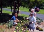 Sr. Elizabeth Jane and volunteers Debbie Klink and Gerri Rhodes plant flowers at Lourdes Grotto